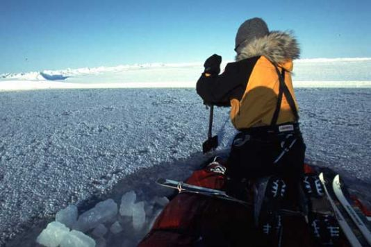 Fully loaded, that is to say in the first weeks of the expedition, the two men could then go on top together, and there still remained - in the lowest part in the middle of the sledges - approximately fifteen centimetres above the water line. In this shot, you can see Alain using the ice shovels as paddles for advancing the craft.